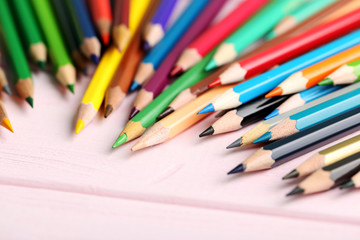Drawing colourful pencils on a wooden background