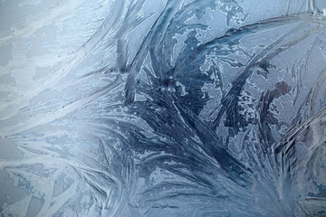 Large frosty patterns on glass in blue tones