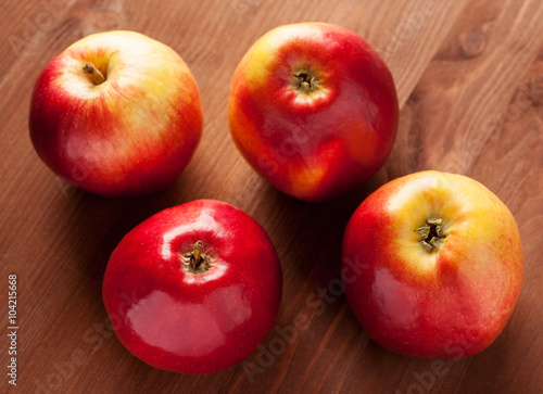 four apples on a brown wooden table stock photo and royalty free