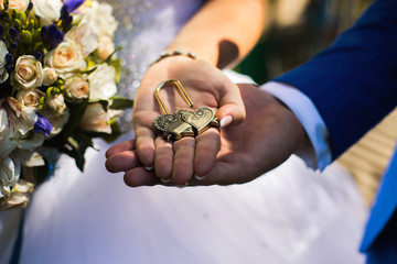 Bride and groom holding lock in their hands, male and female hand with wedding rings, wedding ceremony, together forever, wedding flowers, wedding bouquet