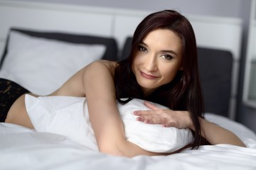 woman posing on the bed with white bedding
