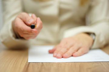 Woman offering pen to sign papers
