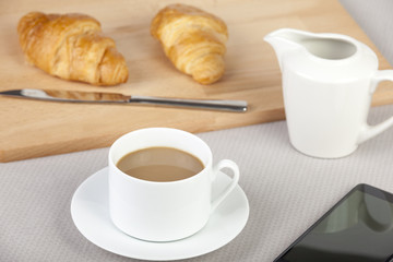 Cup of white coffee with fresh golden croissants