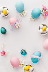 Easter eggs background. Various pastel colored Easter eggs, candies and decorations.