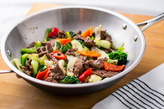 Beef Stir Fry in a wok. Healthy vegetable & beef stir-fry. Made with flank steak, peppers, onions and bok choy stir fried in an asian wok.