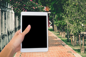 Hands woman are holding touch screen smart phone,tablet on blurred walkway garden nature background.