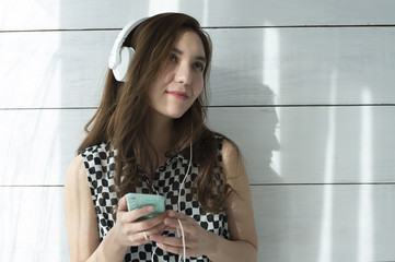 Young woman with a white headphones is riding to music