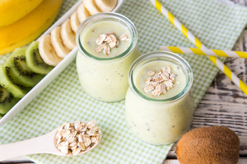 Banana smoothie with kiwi and oats on a light wooden table. Healthy food