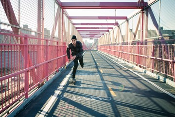 Long shadow of a skateboarder cruising through crosswalk. Photographed in Feb 2016.