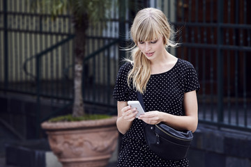 Wall Mural - Blond young woman texting on Smartphone