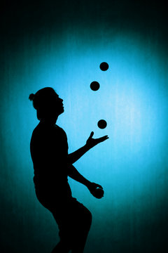 silhouette of a juggler with balls on a blue background