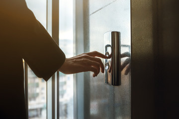 finger presses the elevator button. Red button. sunset light. businessman is a lift. high floor. hand reaches for the button of the elevator call.