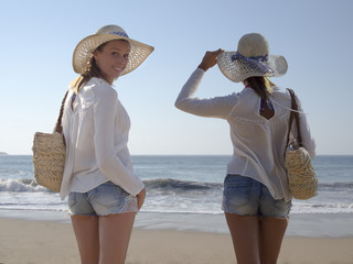twins blonde sisters fashion smiling portrait in the beach  wearing hat and sunglasses