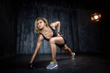 Beautiful muscular woman doing exercise  on a gray background in studio. The front view of sexy young blonde woman workout in the  grange gym.