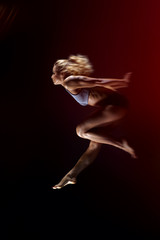 Sport, slim young girl with muscular body  makes a jump on a black background. side view, studio shot, black background.