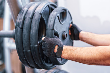man hands holding weight plate in the gym