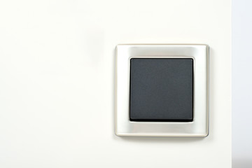 light switch with silver frame on the wall