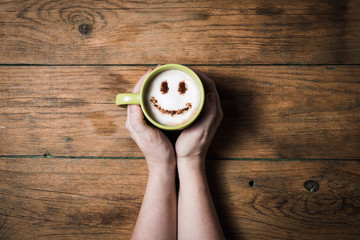 Cappuccino coffee with smiley face on wooden table