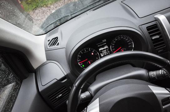 Modern car interior fragment with steering wheel
