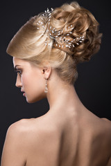 Beautiful blond girl with perfect skin, evening make-up, wedding hairstyle and accessories. Beauty face.