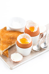 boiled eggs and crispy toasts on a wooden board, vertical