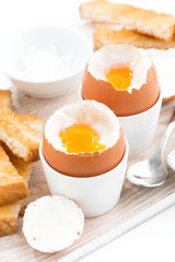 boiled eggs and toasts on a wooden board, vertical
