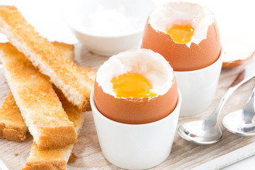 boiled eggs and toasts on wooden board, closeup, selective focus