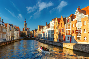 Poster de jardin Bruges Tourist boat on canal Spiegelrei and Jan Van Eyck Square in the morning in Bruges, Belgium