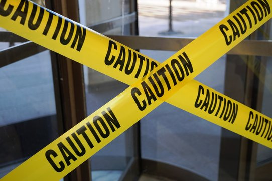 Yellow CAUTION tape barring exit through a door