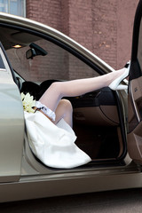 Bride's feet. Bride's leg in a garter, stockings, and a shoe on a car's door.