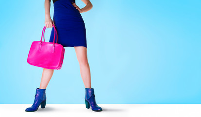 Woman legs with blue short boots, mini skirt, and pink handbag. Isolated on blue background.