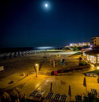 Beleuchteter Strand und Poolbar bei Nacht