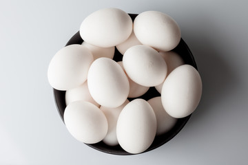 White eggs in a black bowl on white background from above