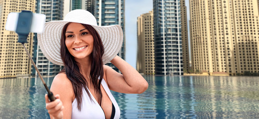 woman taking selfie with smartphone over city pool