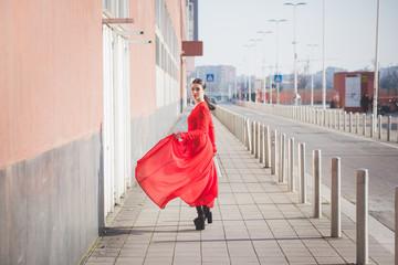 Young beautiful caucasian woman wearing red dress walking in the
