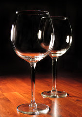 wine glasses on a wooden table, black background