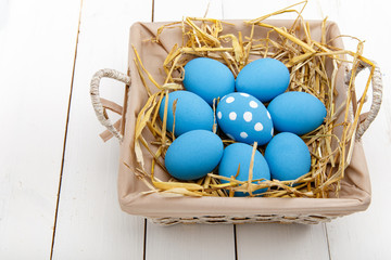 Blue easter eggs in a basket on a white wooden table