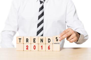 Businessman Arranging Wooden Blocks with Trends 2016 words