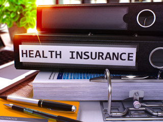 Black Ring Binder with Inscription Health Insurance on Background of Working Table with Office Supplies and Laptop. Health Insurance Business Concept on Blurred Background. 3D Render.