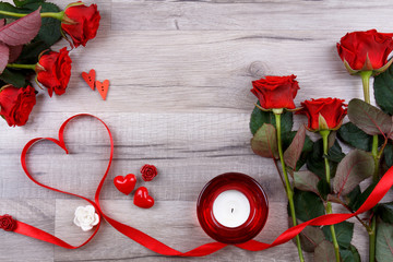 Heart made of red ribbon with red roses, candle and pretty little hearts on wooden board. Valentines day background