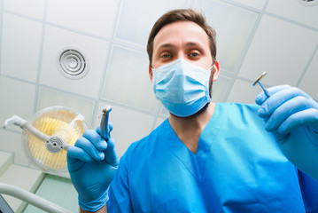 Dentist leaned over patient in dentist's chair at clinic. Doctor with mask and tools