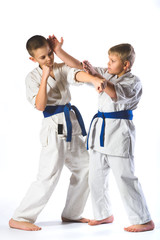 boys in kimono during training karate exercises on  white background