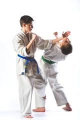 boys in kimono during training karate exercises on  white background