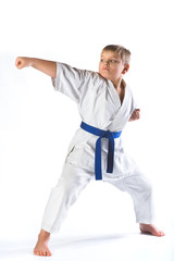 boy in kimono during training karate exercises on  white background