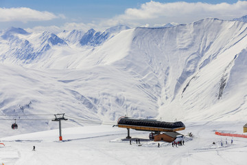 Panoramic view on ski station on snowy mountains background