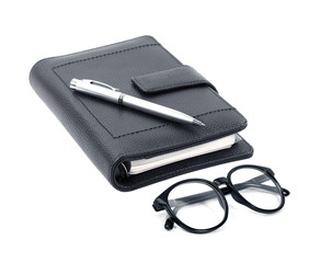 notebook with pen and glasses isolated on white