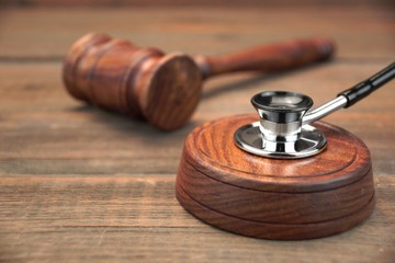 Stetoscope and Real Judges Gavel On Brown Wooden Background