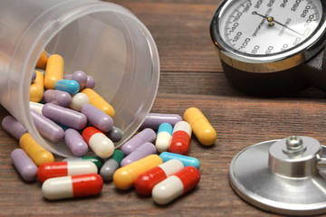 Medical Devices and Scattered From Vial Pills on Wooden Table