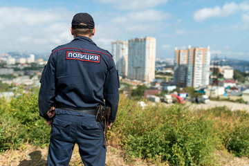 "Police officer looking at city. Inscription ""Police"" on the uniform of russian police."