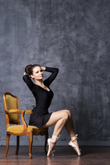 Young and beautiful ballerina with a perfect body sitting on a vintage armchair.